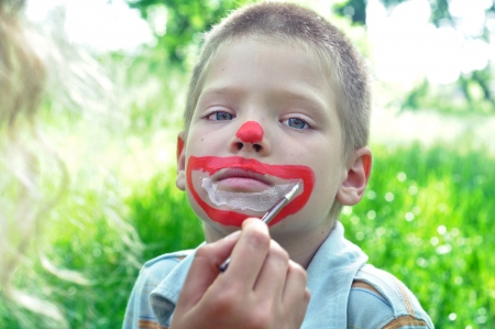 'face painting': outdoor portrait of a child with his face being painted