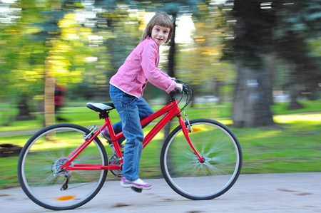 Elementary age  child riding red l bike in fall park. Motion blur. Stock Photo - 16084252