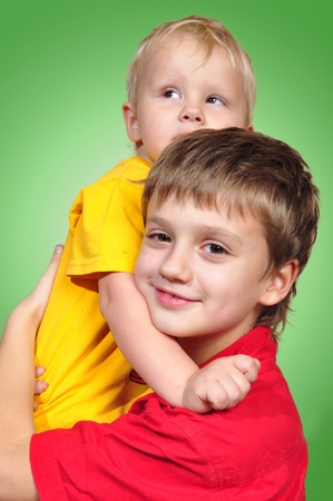 smiling loving brothers against green background Imagens