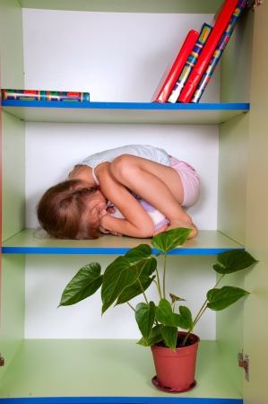 hide: little girl hugging her toy and hiding in a closet