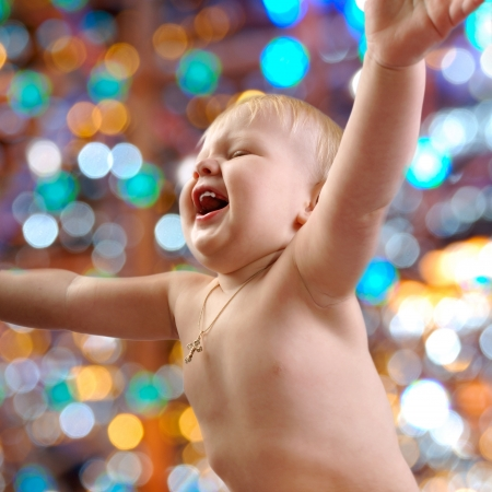 brightly colored: portrait of a happy baby against  coloful shiny background