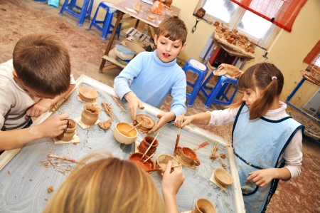 group of children 7-9 years old shaping clay in pottery studio photo