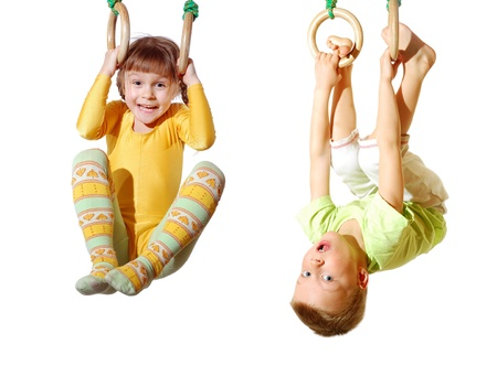girl with rings: preschool children playing and exercising on gymnastic rings