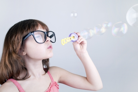 child with glasses blowing soap bubbles photo