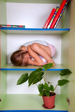 little girl hugging her toy and hiding in a closet photo