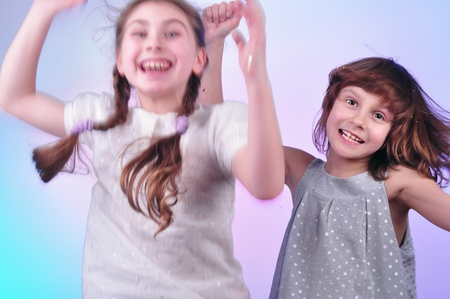 studio portrait of two joyful children having fun and dancing photo