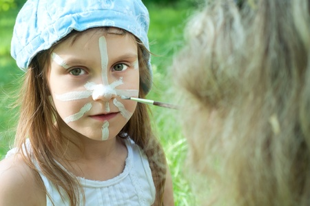 painted face mask: child with a mask painted on her face