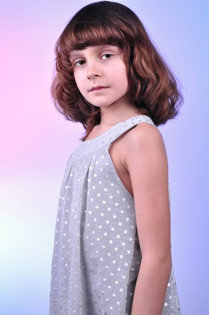 8 year old girl: studio shot of a pretty 8 year old girl in silver dress