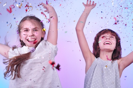 studio portrait of two joyful girls having fun and dancing photo