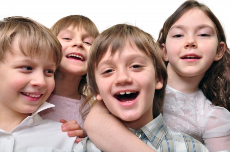 Studio portrait of a group of four happy smiling elementary age children  Best friends  Isolated over white  photo