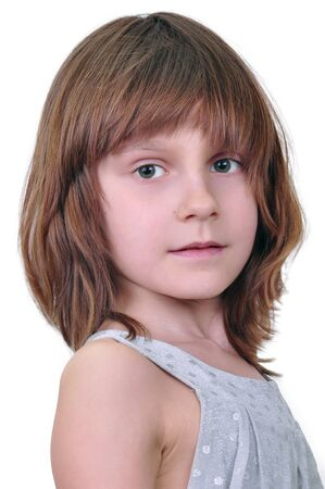 emotionless: Portait of an elementary age girl looking at camera with serious face expression  Isolated over white