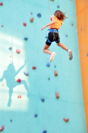 niño trepando: Niña de 8 años de edad se desliza por la pared de escalada Foto de archivo