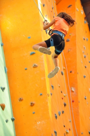 8 years old girl  child sliding down the  climbing wall photo