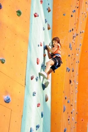 niño trepando: niño que sube por la pared de la escuela de escalada