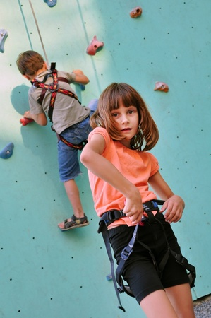 elementary children with climbing equipment against the training wall photo