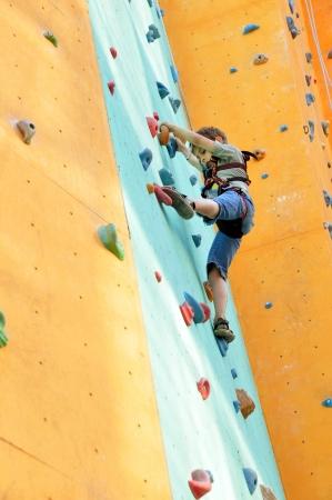 niño escalando: 6 años del muchacho que sube por la pared Foto de archivo