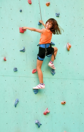 smiling 8 years old girl  climbing up the wall Stock Photo