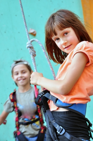climbing sport: elementary children with climbing equipment against the training wall Stock Photo