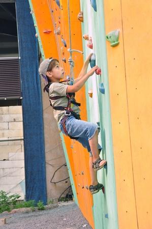 niño escalando: Niño de 6 años subiendo por la pared