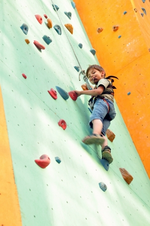 smiling elementary child climbing up the wall