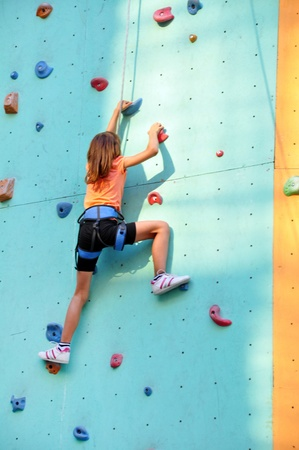 8 years old girl  climbing up the wall photo