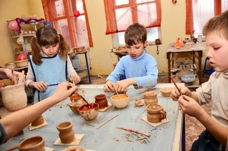 jonge kinderen versieren hun handgemaakte klei aardewerk