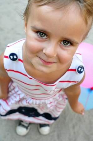 portarit: close-up portarit of  adorable little girl smiling and playing with colurful balloons looks up Stock Photo