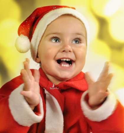 Christmas portrait of a toddler child clapping hands against bright background photo
