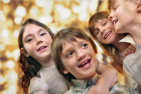 Holiday portrait of happy children against bright golden background. Studio shot. photo