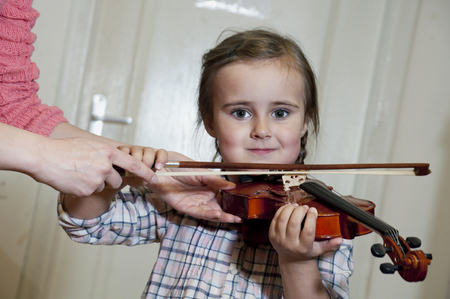 cute 3 year old preschool girl learning violin playing at music school photo