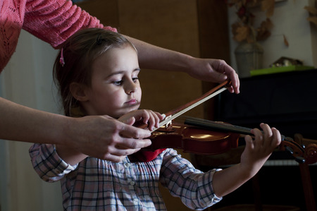 Adorable 3 year old little girl learning  playing violin at music school class. First steps. Standard-Bild