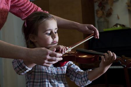violines: Adorable aprendizaje de 3 a�os ni�a tocando el viol�n en la clase de la escuela de m�sica. Primeros pasos.