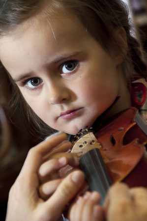 3 year old: Adorable 3 year old little girl learning  playing violin on music school class. First steps. Stock Photo