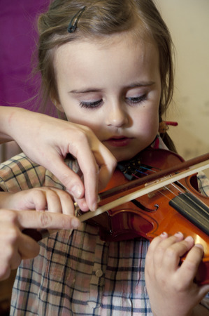 Adorable 3 year old little girl learning  playing violin on music school class. First steps. photo