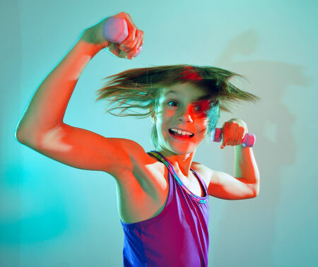 adorable little elementary girl  exercising with dumbbells photo
