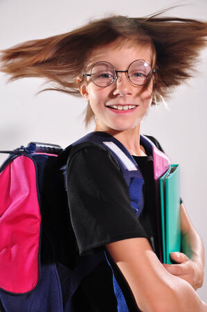 Back to school. Happy smiling wearing eyeglasses schoolchild with a schoolbag. photo