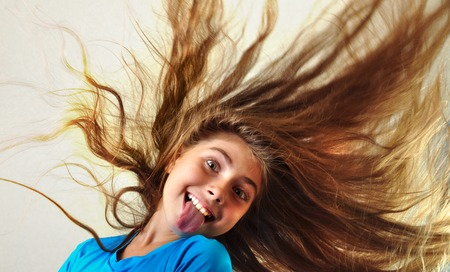 sacar la lengua: adorable ni�o con largo pelo flotante sacando la lengua Foto de archivo