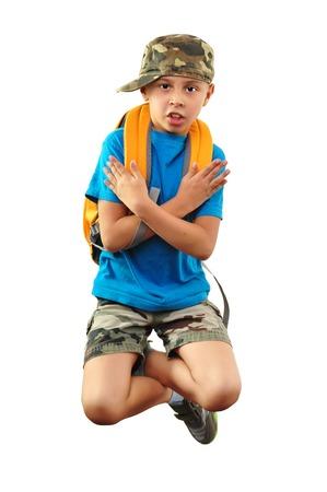 niño con mochila: Las piernas y los brazos cruzados niño con mochila y una gorra de baile y saltos. Aislado sobre fondo blanco.