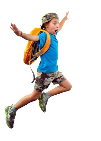 Full length portrait of a little boy with backpack and a cap running, jumping, waving with his hand and shouting. He is about ro fall down.  Human emotion, facial expression,scared, worried, being late, stress,  Isolated over white background. Standard-Bild