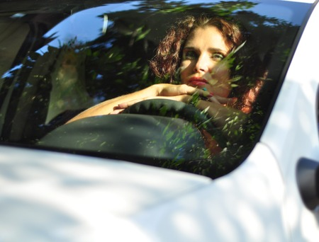 impatient: Portrait of young beautiful brunette Caucasian woman in her white car looking bored. Urban reflection on the window. Traffic jam concept, negative human emotion concept Stock Photo