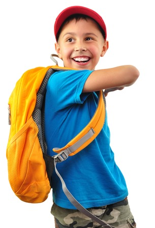 Portrait of a cute happy smiling little boy with yellow backpack and a red cap looking back. Isolated over white background photo