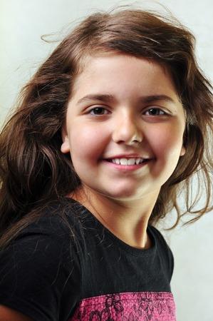 lengua afuera: adorable niño con largo pelo flotante sacando la lengua Foto de archivo