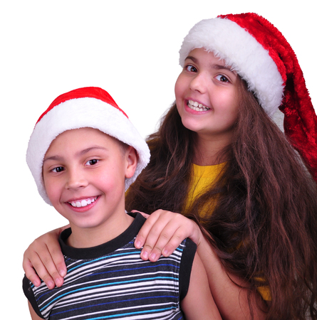 Two happy children with Santa Claus red hats photo