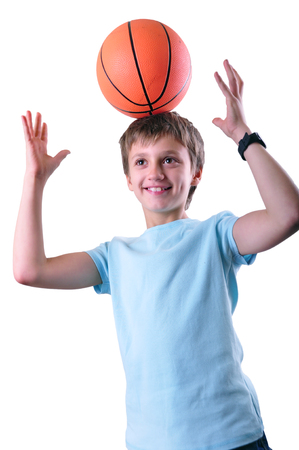 boy basketball: Caucasian smiling boy, basketball player having fun with a ball on his head isolated on white background. Stock Photo