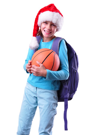 Child with Santa Claus red hat and ball. Christmas, New Year, holiday activities, sports celebration photo