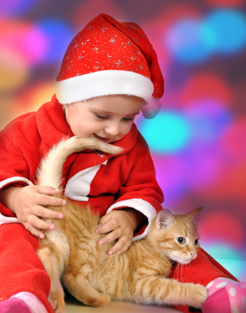 Happy small girl in Christmas  Santa red hat playing with a small kitten photo