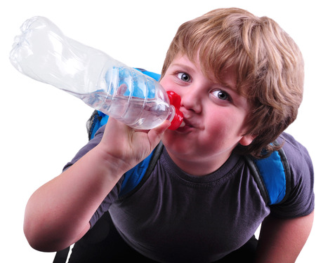 Closeup ortrait of cute schoolboy drinking water. Isolated over white background photo