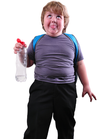 Closeup portrait of cute schoolboy drinking water. Isolated over white background photo