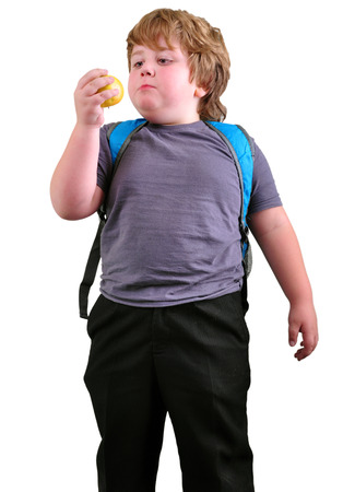 portrait of cute schoolboy eating apple. Isolated over white background photo