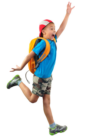 scared boy: Full length portrait of a little boy with backpack and a cap running, jumping, waving with his hand and shouting. He is about ro fall down.  Human emotion, facial expression,scared, worried, being late, stress,  Isolated over white background. Stock Photo
